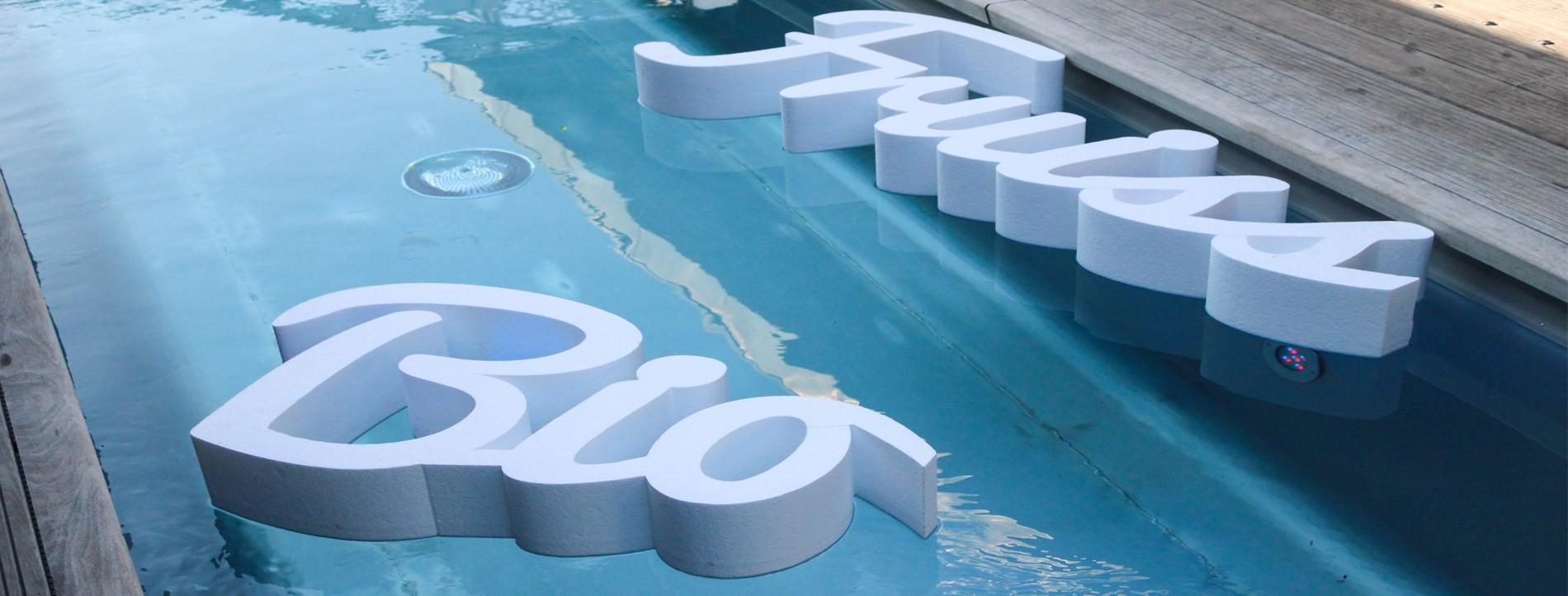 Logo géant Fruiss Bio en polystyrène blanc brut flottant sur une piscine